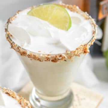 coconut lime margarita with a toasted coconut rim and lime garnish