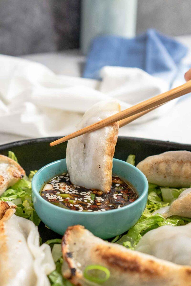dunking a potsticker into gyoza sauce