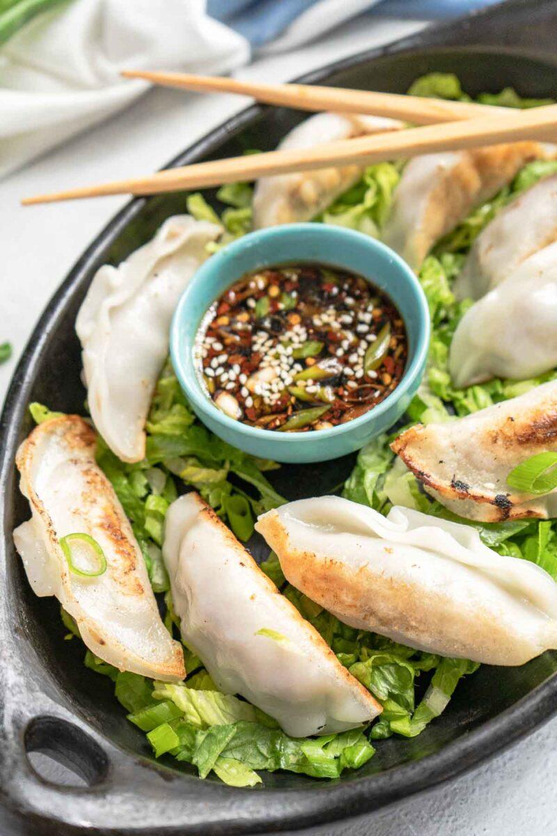 plate of dumplings with a bowl gyoza sauce and chopsticks