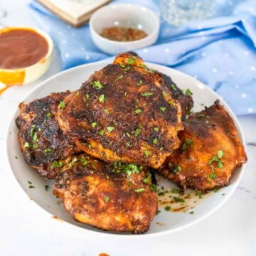 grilled BBQ chicken on white plate with blue table cloth