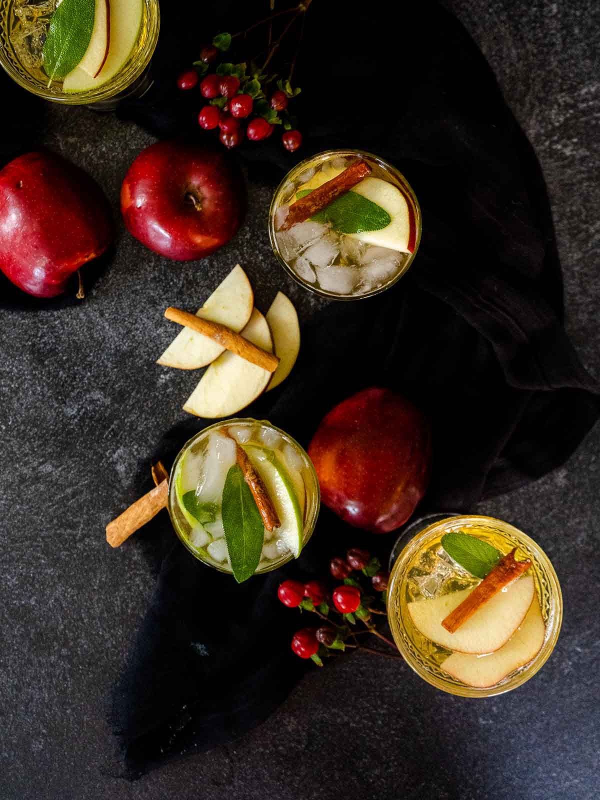 apples and cinnamon sticks with whiskey cocktail on black background