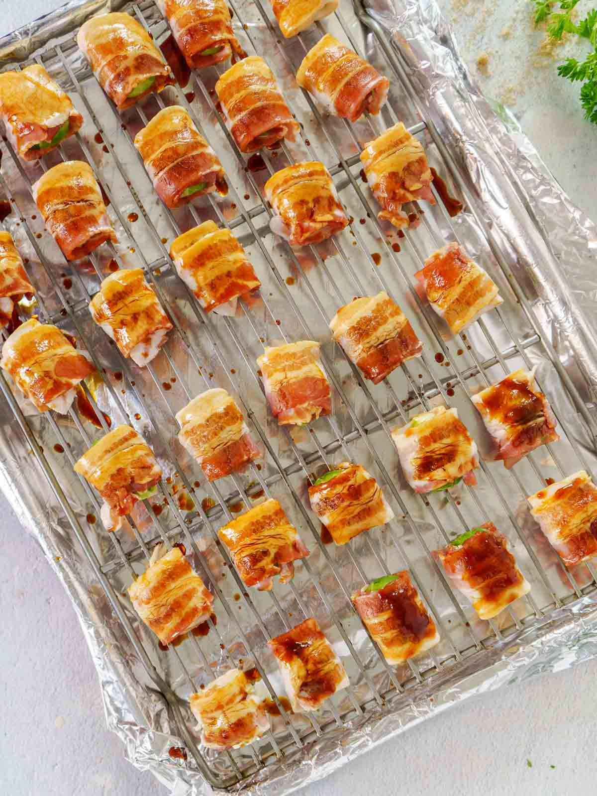 glazed bacon wrapped brussels sprouts on wire rack above lines sheet pan