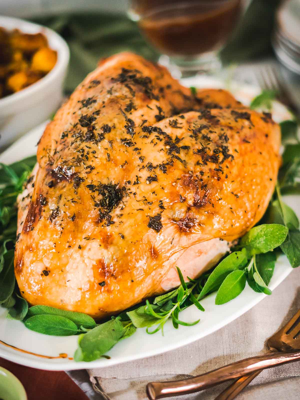herb roasted turkey breast on a platter with fresh herbs