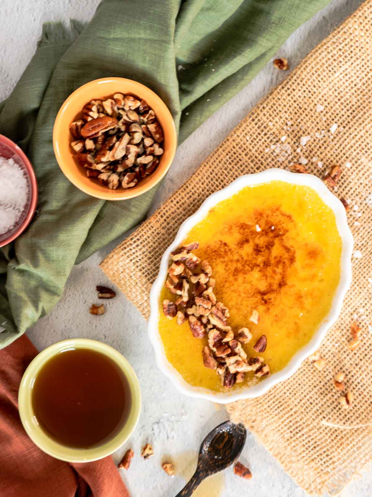 creme brulee with bowls of pecans and maple syrup