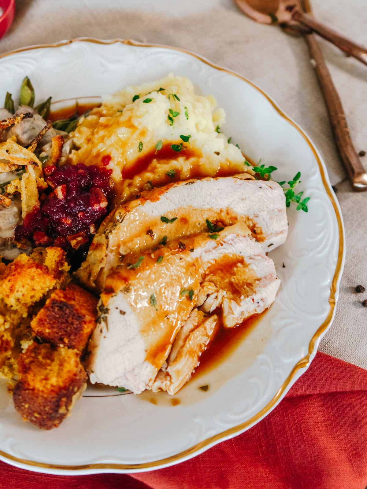 plate full of thanksgiving staples including turkey breast with gravy